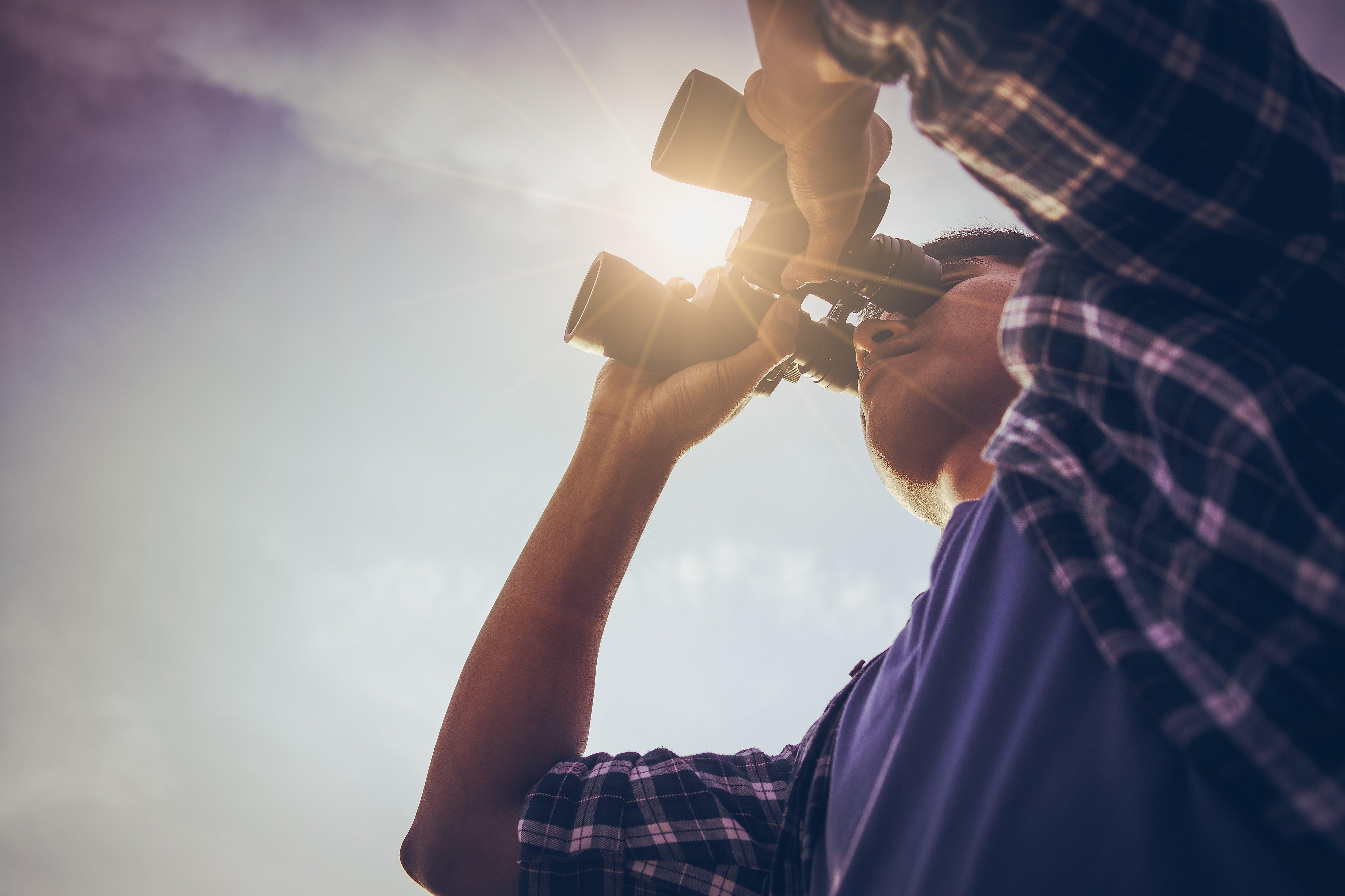 close-up-asian-man-hand-using-binoculars